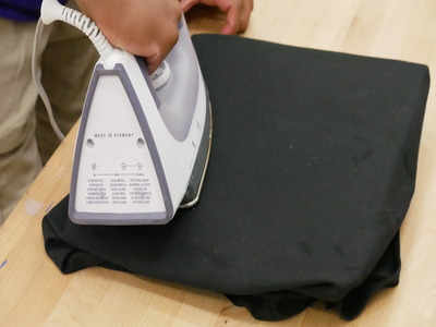 photo showing how to iron the shirt after cardboard is in place to get rid of wrinkles