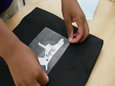 photo showing vinyl stencil being applied on the shirt