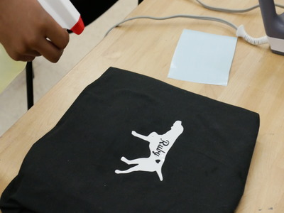 photo showing bleach being applied to shirt over the stencil