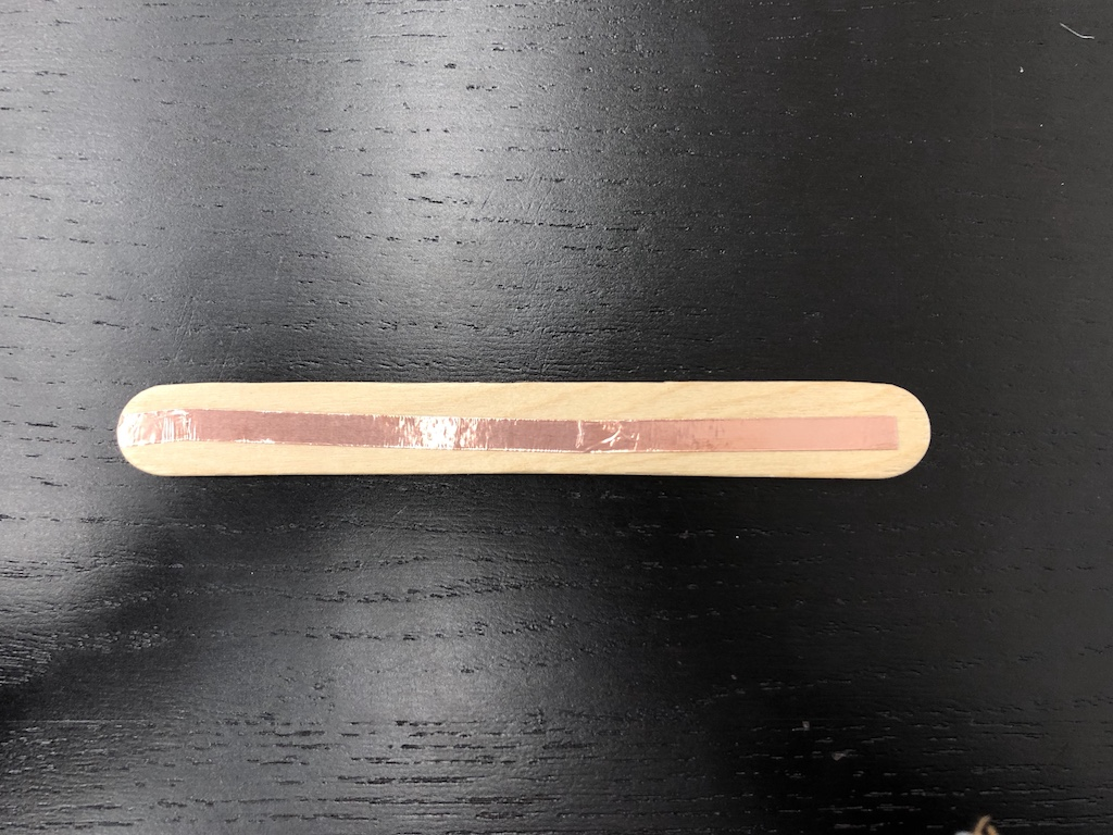 jumbo craft stick with copper tape adhered to one side