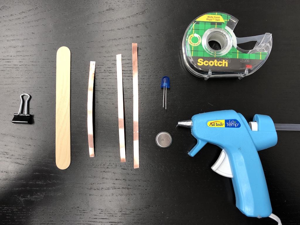 supplies: 10mm LED, jumbo craft stick, coin cell battery, copper tape, small binder clip, scotch tape, hot glue gun