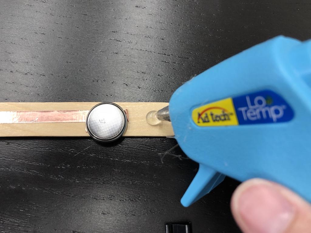using a hot glue gun to add a drop of hot glue under the black base of the binder clip to attach to craft stick