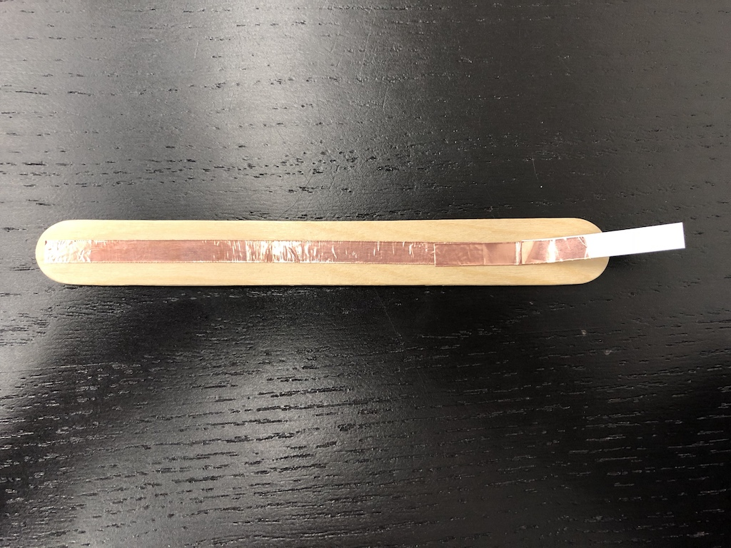 opposite side of jumbo craft stick with copper tape adhered longer than length of stick