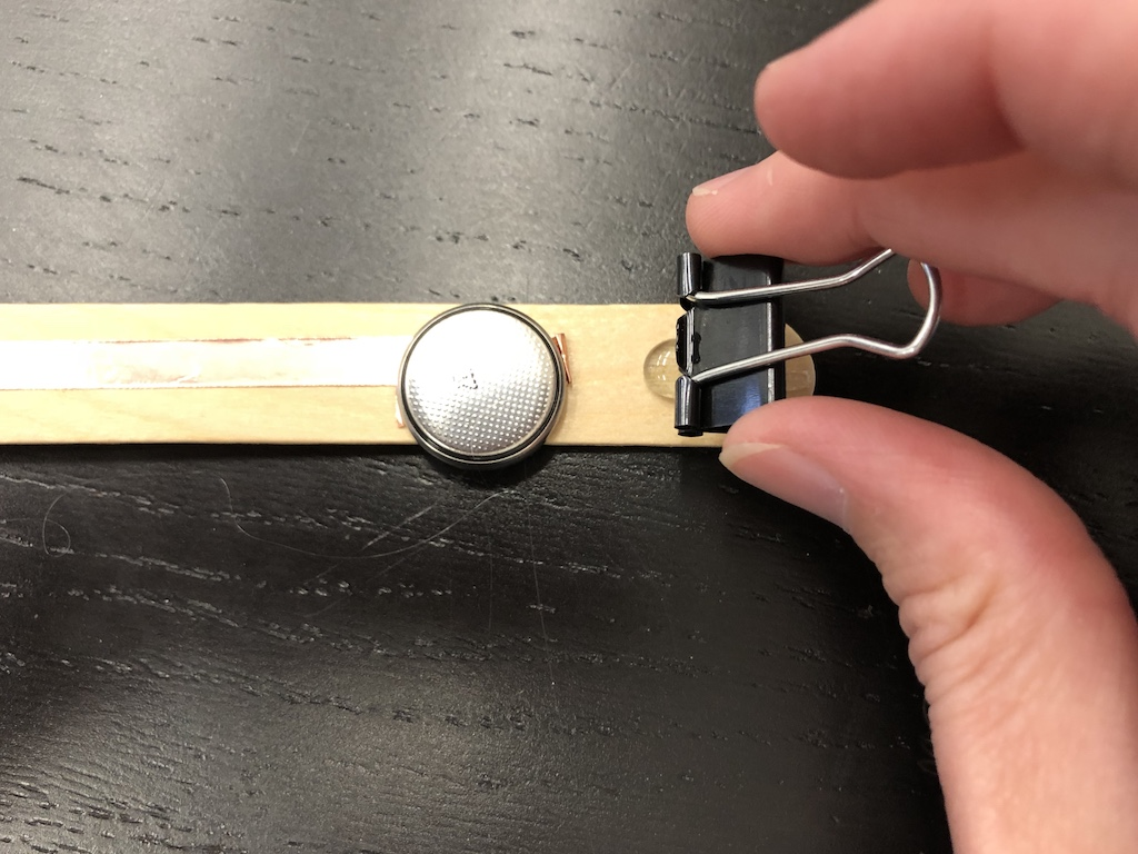 pressing binder clip into hot glue to secure to craft stick