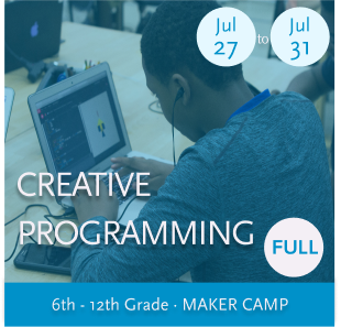 Game Development With Unity Maker Camp -- Youth taking notes at a table while working with a computer